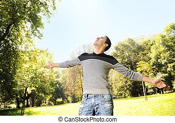 debout, parc, jeune, mains, ouvert, homme