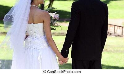debout, parc, nouveaux mariés, tenant mains