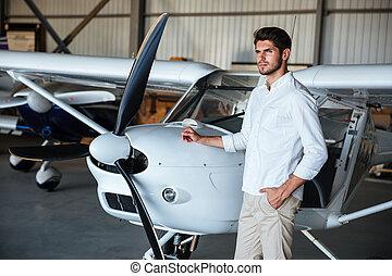 debout, petit avion, homme, sérieux