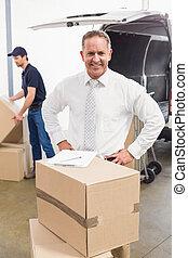 debout, pile, boîtes, directeur, sourire, derrière, carton