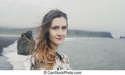 debout, plage, femme, appareil photo, jeune, islande, regarder, orteils, arrière-plan noir, portrait, sourire, troll
