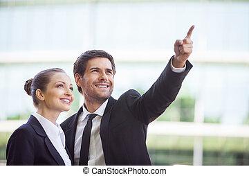 debout, pointage femme, professionnels, jeune, quelque chose, portrait, dehors., homme souriant