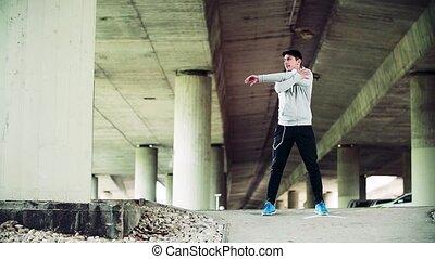 debout, pont, sportif, stretching., jeune, sous, ville, homme