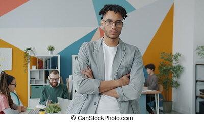 debout, portrait, african-american, bras, sérieux, homme affaires, bureau, traversé