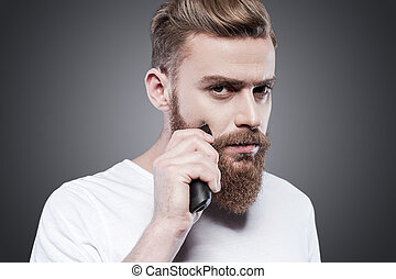 debout, rasoir, barbu, sien, électrique, appareil photo, gris, contre, jeune regarder, confiant, quoique, perfect., barbe, fond, confection, homme, rasage