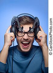 debout, rigolote, beau, headphones., bleu, jeune, fond, portrait, type, homme, lunettes