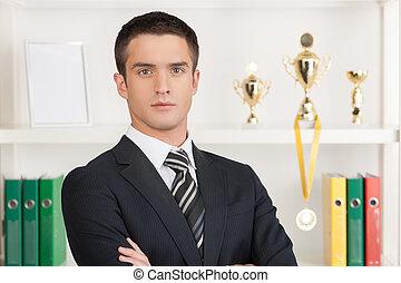 debout, sien, business, armes traversés, trophées, jeune, confiant, businessman., tenue, devant, homme affaires