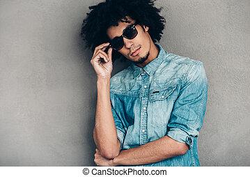 debout, sien, lunettes soleil, ajustement, jeune, contre, gris, regarder, confiant, quoique, appareil photo, calme, fond, africaine, stylish., homme