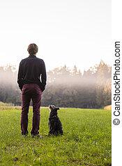 debout, sien, pré, séance, chien, jeune regarder, milieu, vert, noir, lui, homme