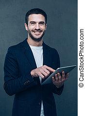 debout, sien, tenue, tablette, tablet., jeune, contre, gris, gai, quoique, fond, numérique, nouveau, sourire, apprécier, homme