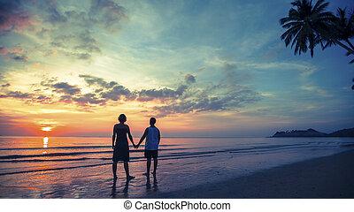 debout, silhouette, couple, lune miel, jeune, leur, surprenant, mer, plage, sunset.