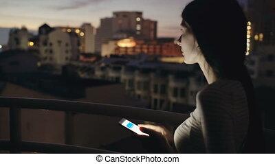 debout, smartphone, toit, texting, jeune femme, closeup, terrasse, nuit, sourire