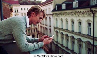debout, smartphone, ville, texting., jeune homme, balcon