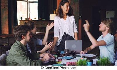 debout, sourire., workgroup, gens bureau, business, concept., hommes, jeune, élevé, conversation, quoique, cinq, alors, pendant, table, réunion équipe, éditorial, femmes