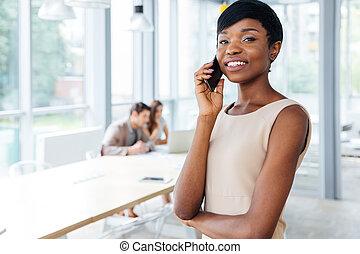debout, téléphone bureau, femme affaires, cellule, conversation, heureux