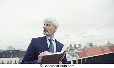debout, terrasse, agenda, mûrir, homme affaires, writing.