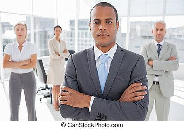 debout, traversé, homme affaires, bras, sérieux