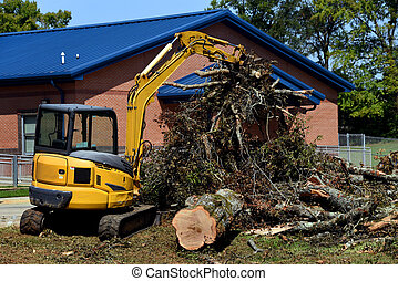 Excavator with claws has a bucket full of branches and limbs from a fallen tree besides a school in Ruston, Louisiana.