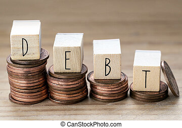 Debt written on wooden cubes with letters, money piles of coins, money climbing stairs wooden background, business concept