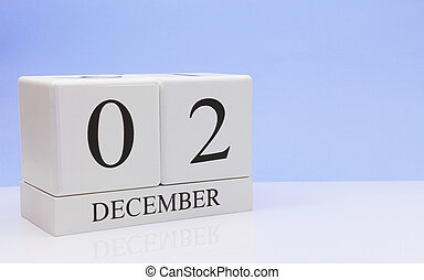 December 02st. Day 2 of month, daily calendar on white table with reflection, with light blue background. Winter time, empty space for text