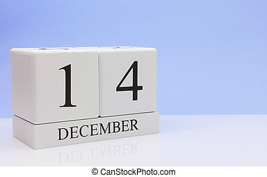 December 14st. Day 14 of month, daily calendar on white table with reflection, with light blue background. Winter time, empty space for text
