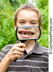 Young boy showing missing baby tooth through hand magnifier, shallow DOF