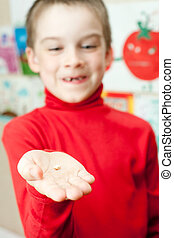 Boy with deciduous tooth in his hand, shallow focus