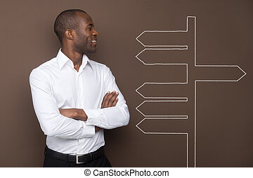 Decisions - Young businessman looking at many arrows on the...