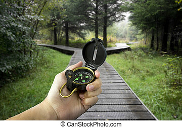 decisions - man holding compass with two paths ahead