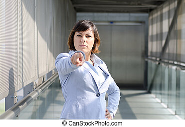 Decisive business woman standing up and pointing at you