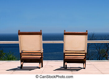 deck chair - Two deck empty deck chairs facing the sea