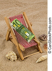 a deck chair with a euro bank note. symbolic photo for save on vacation and while traveling