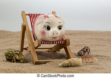 deck chair with piggy bank on the sandy beach. symbolic...