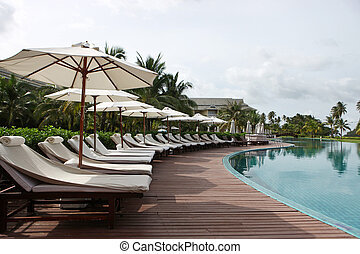 Deck chairs and umbrellas next to a swimming pool.