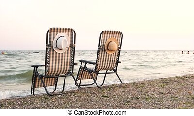 Deck chairs on beach seashore. Attached hats. Rear back...