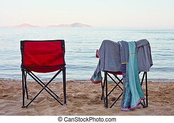 Deck chairs - Two fold up deck chairs on a sandy beach at...