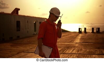 Deck Officer on deck of offshore vessel holds VHF...