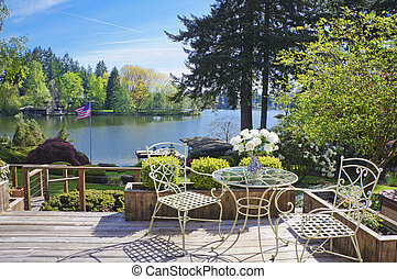 Deck with chairs and table with lake view.
