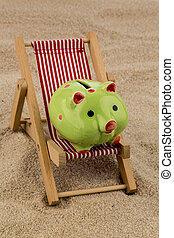 deckchair with piggy bank on the sandy beach. symbol photo...