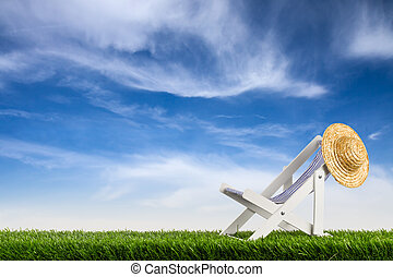 deckchair with straw hat on meadow