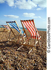deckchairs on beach on windy day in brighton. pebble costline or seashore in england with outdoor sun relaxing chair furniture