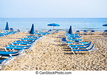 Deckchairs on the beach sand at sunset