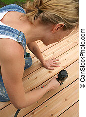 A girl uses an air gun to nail her new deck.