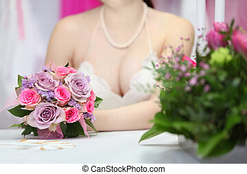 decollete of young bride, which sits at table with candles...
