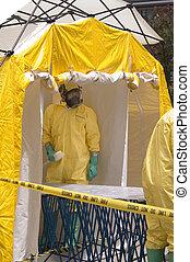 A hazmat crew member awaiting a victim in a decontamination shower.