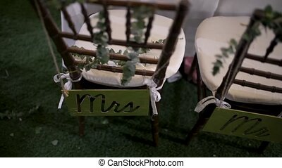 Decor at the wedding, the chairs of the bride and groom with signs