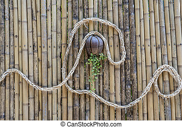 Decorated bamboo wall with a rope and a coconut flower pot on a tropical beach in Thailand