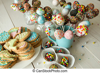 Decorated cake pops and cookies for Easter on wooden table -...