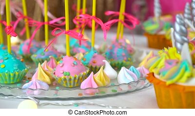 Decorated children's birthday party. Unicorn themed treats, close-up against colorful background.