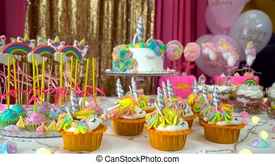 Decorated children's birthday party with tasty cupcakes, colourful lollipops and unicorn cake